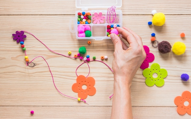 Close-up da mão fazendo colar com miçangas; flor e bola de algodão no pano de fundo texturizado de madeira