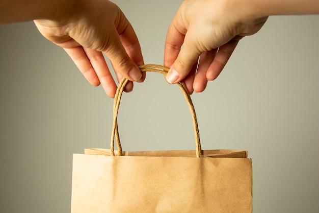 Close up da mão fêmea que guarda o pacote de papel do ofício, zombaria do projeto acima. conceito zero easte.