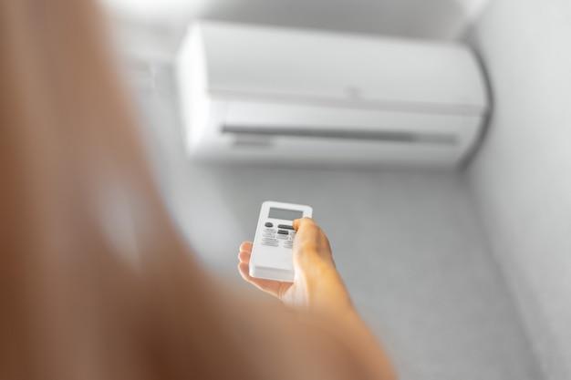 Close-up da mão feminina ajustando o ar condicionado com controle remoto.