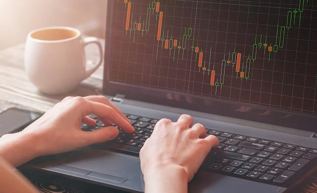 Close-up da mão feminina de um corretor do mercado de ações, analisando o gráfico no laptop.