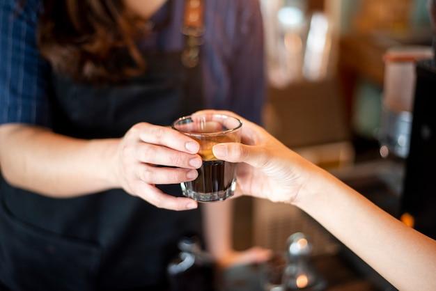 Close up da mão feminina está tomando café quente de barista