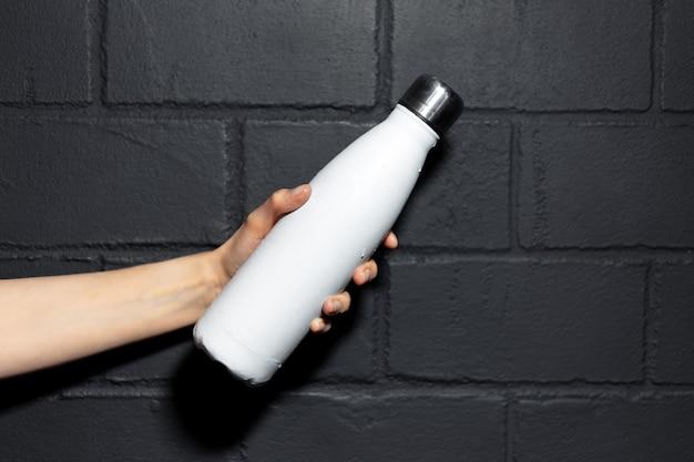 Close-up da mão feminina, segurando a garrafa de água térmica reutilizável de aço, de cor branca, sobre fundo de parede de tijolo preto.