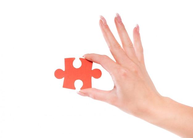 Close-up da mão feminina segurando o quebra-cabeça.