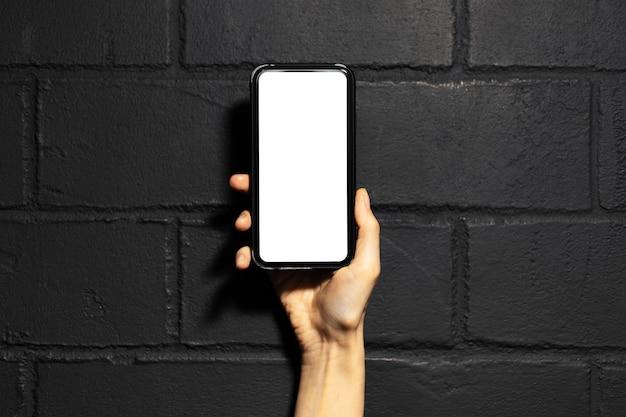 Close-up da mão feminina segurando um smartphone com maquete, no fundo da parede de tijolo preto.