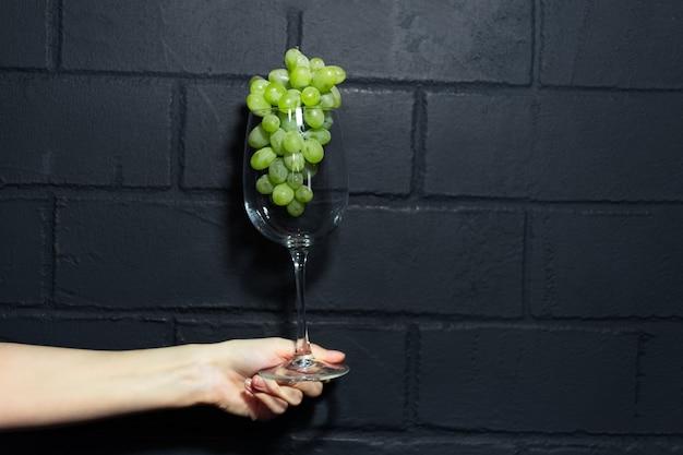 Close-up da mão feminina segurando uma taça de vinho com uvas verdes dentro no fundo da parede de tijolo preto.