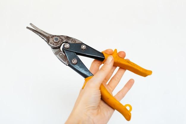 Close-up da mão feminina segurando uma tesoura industrial para metal em branco.