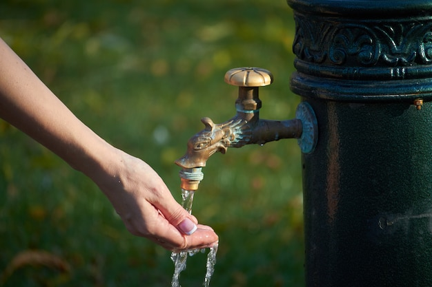 Close-up da mão feminina sob a água de uma coluna de estilo antigo com água potável em um parque de outono, foco seletivo
