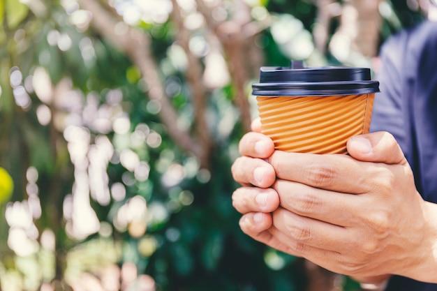 Close-up da mão masculina que guarda uma xícara de café de papel para levar embora.