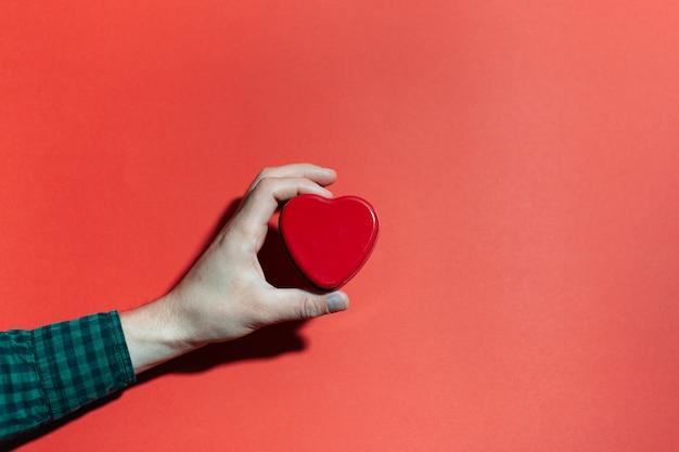 Close-up da mão masculina segurando a forma de um coração vermelho na superfície da cor vermelha.