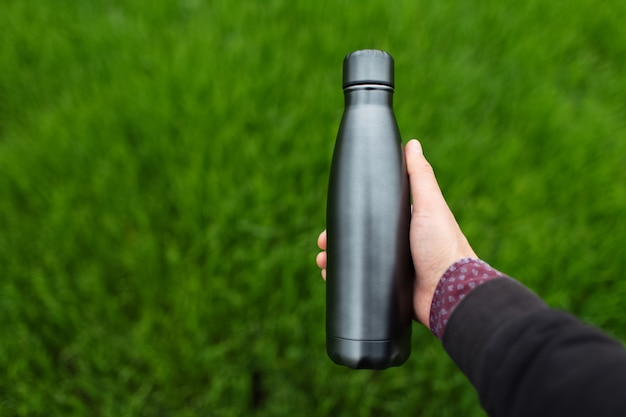 Close-up da mão masculina segurando a garrafa de água térmica reutilizável de aço no fundo da grama verde turva com espaço de cópia.