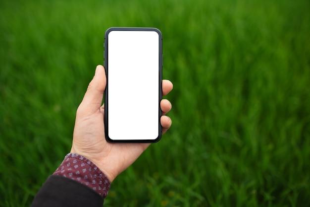 Close-up da mão masculina segurando o smartphone com maquete no fundo da grama verde turva com espaço de cópia.