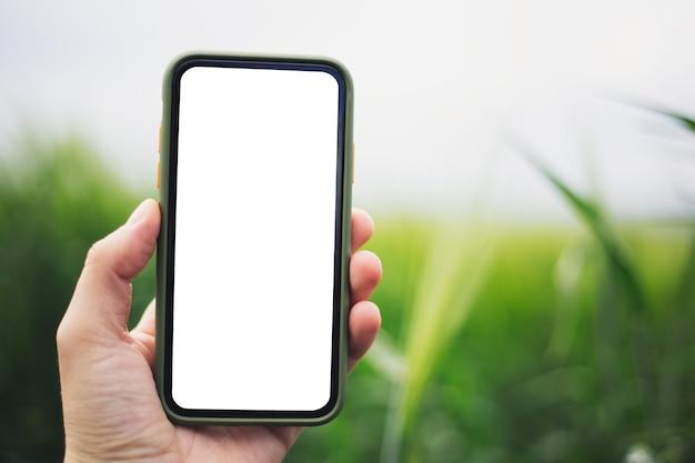 Close-up da mão masculina segurando o smartphone com maquete no fundo desfocado ao ar livre.