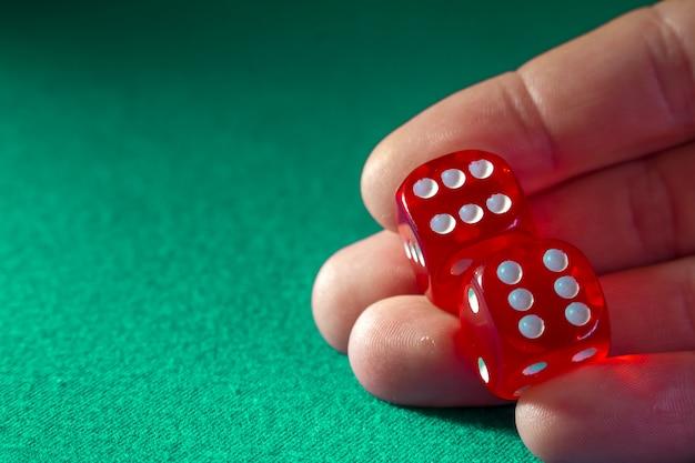 Close up da mão que guarda dados vermelhos com uma combinação de vencimento no pano verde em um casino.