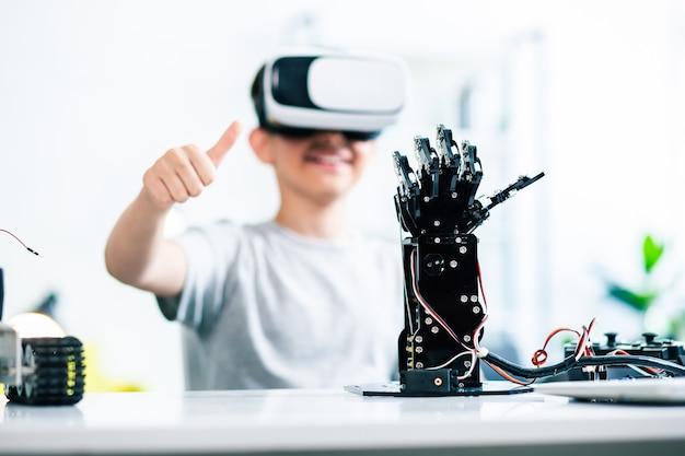 Close-up da mão robótica em pé sobre a mesa enquanto um garotinho inteligente a controla enquanto prepara seu projeto de engenharia