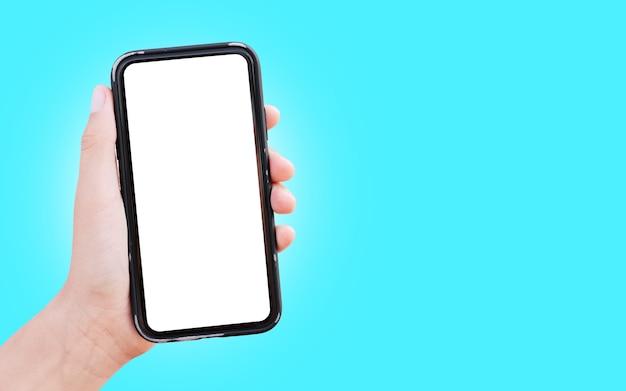 Close-up da mão segurando o smartphone com maquete branca isolada na superfície da cor ciano.