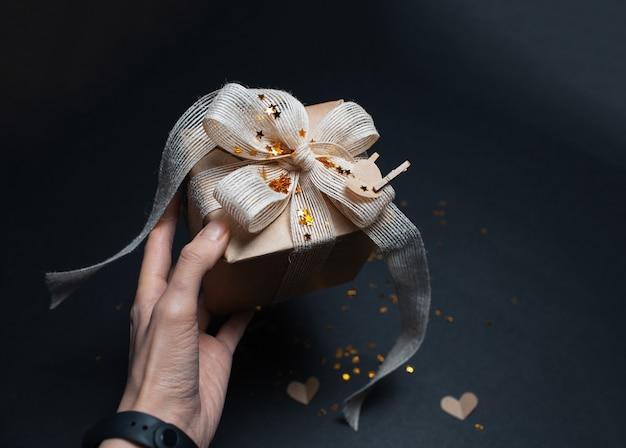 Close-up da mão segurando uma caixa de presente ecológica na superfície preta