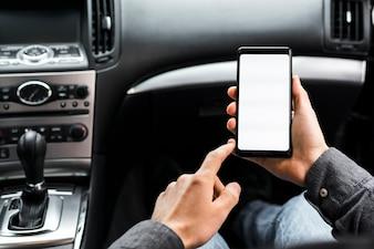 Close-up da mão usando smartphone com tela branca, sentado no carro
