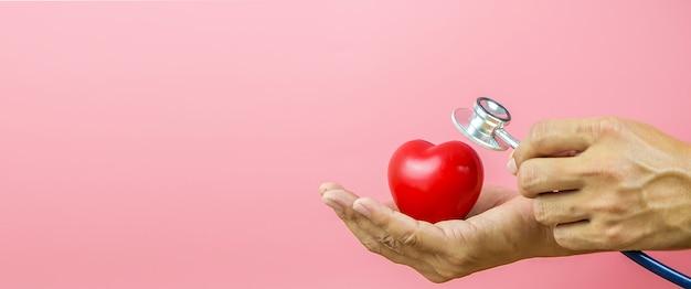 Close-up da mão usando um estetoscópio para verificar o coração.