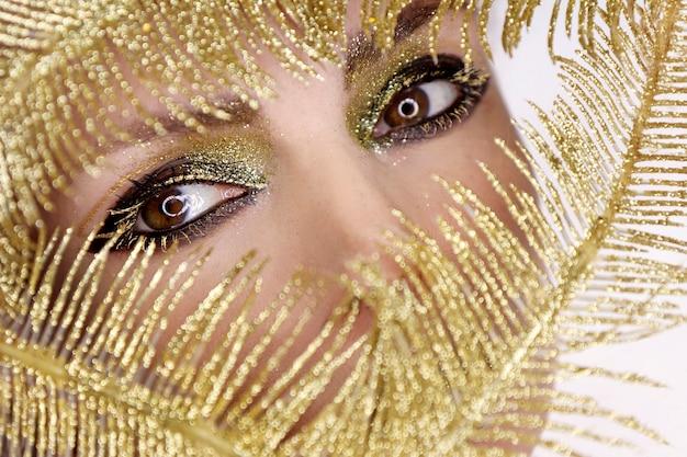 Close-up da maquiagem dos olhos da festa à noite com joias brilhantes douradas.