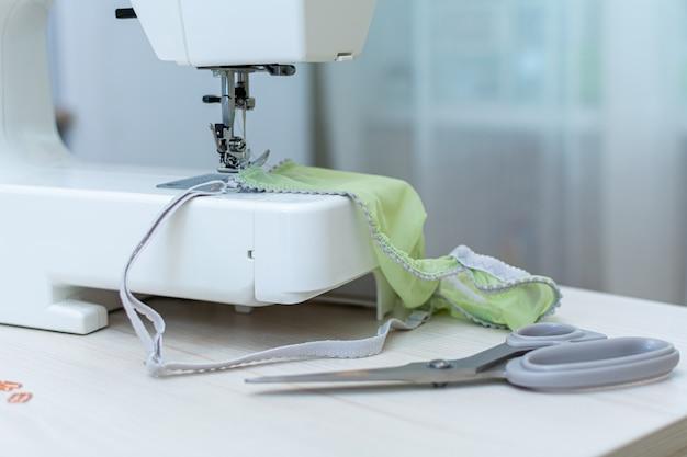Close-up da máquina de costura branca, ao lado de uma tesoura com alças cinza.