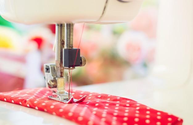 Close-up da máquina de costura, trabalhando com tecido vermelho