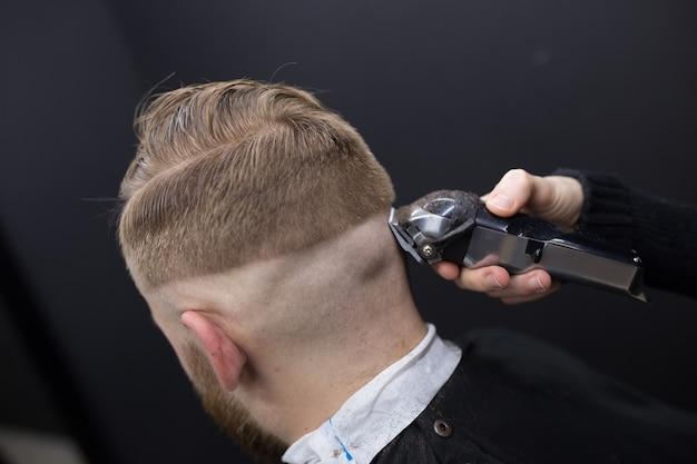 Close-up da máquina de escrever de homens de corte de cabelo. barber corta um homem.