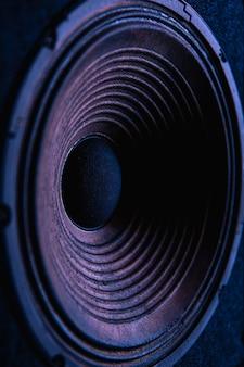 Close-up da membrana do alto-falante em fundo preto com iluminação colorida.