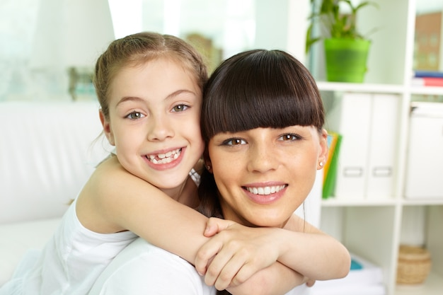 Close-up da menina abraçando sua mãe