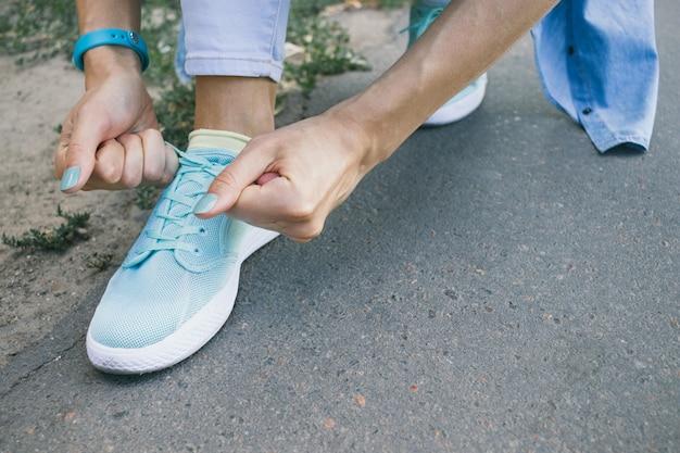 Close-up da menina amarra os laços nos sapatos enquanto caminhava pela cidade