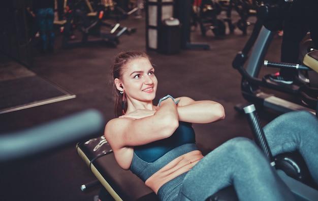 Close-up da menina atlética sorridente no sportswear fazendo exercícios de flexão nos músculos abdominais