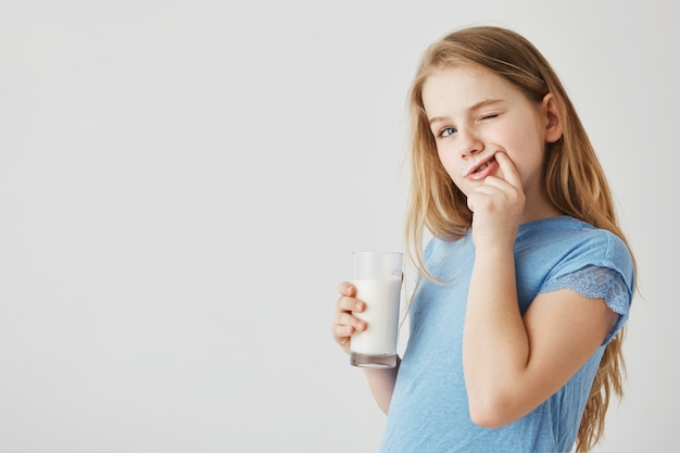Close-up da menina bonitinha de olhos azuis parece de lado, bebendo copo de leite e limpando os dentes após uma refeição com o dedo. infância despreocupada.
