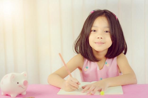 Close-up da menina bonitinha escrevendo livro
