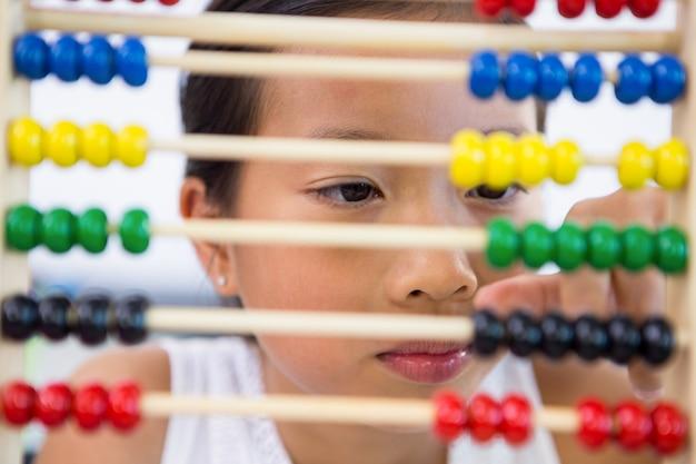Close-up da menina brincando com o ábaco