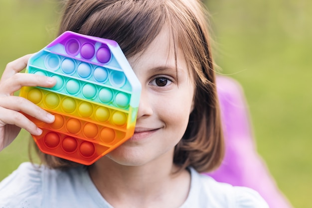 Close-up da menina com pop it toy simples covinha na moda antistress brinquedo sensorial nas mãos das crianças