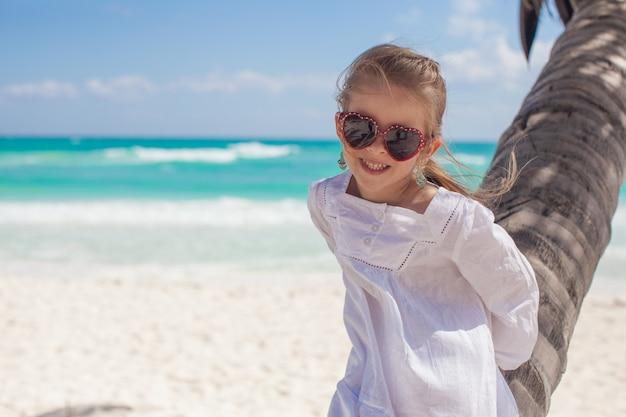 Close up da menina de sorriso que senta-se na palmeira na praia do cararibe perfeita