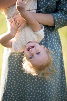 Close-up da menina de sorriso que tem o divertimento com sua mãe