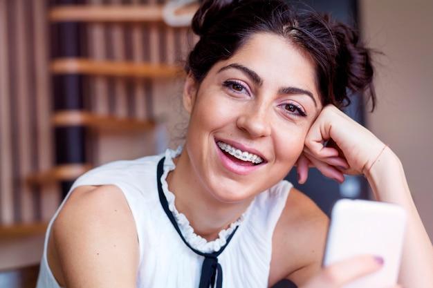Close-up da menina feliz com o seu celular