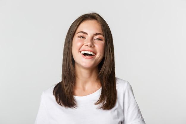 Close-up da menina morena feliz em t-shirt branca, rindo e sorrindo despreocupada para a câmera.