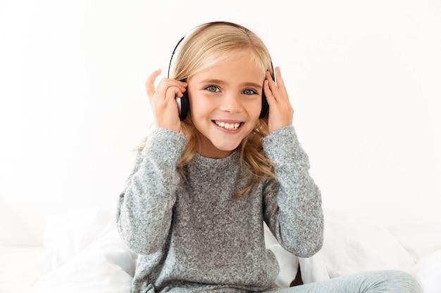Close-up da menina muito sorridente, tocando seus fones de ouvido enquanto ouve música,