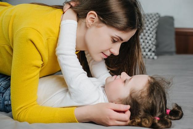 Close-up da menina pré-escolar, deitado na cama confortável, brincando com a sorrir jovem mãe amorosa em casa, alegre mãe abraça a filha pequena bonita, rir aproveite o fim de semana no quarto brincando se divertindo juntos