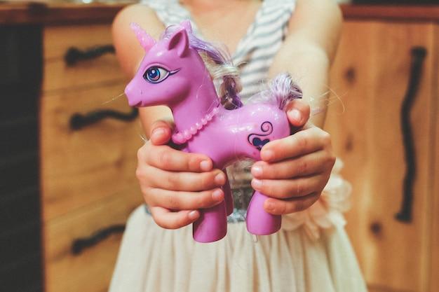 Close-up da menina que mostra seu brinquedo