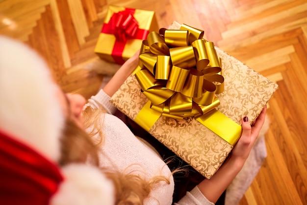 Close-up da menina segurando as mãos uma caixa grande com um grande laço dourado com um presente.