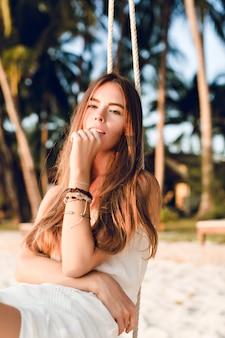Close-up da menina tenra, sentada em um balanço, usando um vestido branco. ela tem longos cabelos escuros. ela tem pulseiras no braço. o balanço é na praia com palmeiras verdes