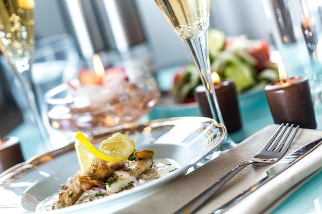 Close-up da mesa com comida, pratos, velas e taças de champanhe