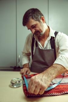 Close-up da mesa de alfaiates com mãos masculinas, traçando padrão de tecido para roupas no atelier tradicional. o homem na profissão feminina. conceito de igualdade de gênero