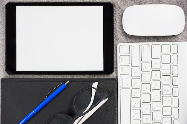 Close-up da mesa de escritório com tablet digital; rato; teclado; caneta; óculos e diário na mesa