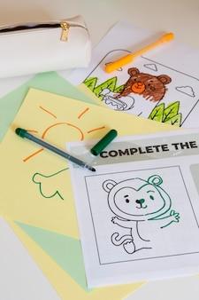Close-up da mesa infantil com desenho e canetas