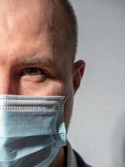 Close-up da metade do rosto de um homem em uma máscara médica em um fundo cinza. foto vertical
