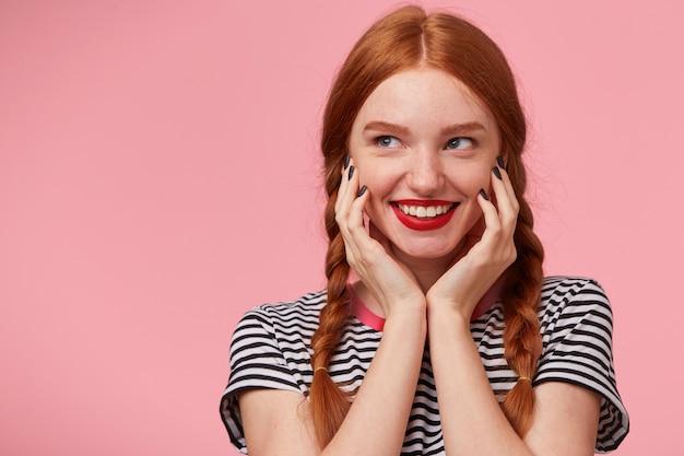 Close-up da misteriosa encantadora garota ruiva bonita com duas tranças mantém as mãos perto do rosto e sorrindo animadamente com lábios vermelhos, olhando para o lado esquerdo no espaço da cópia, isolado