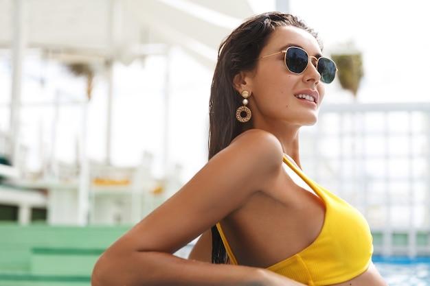 Close-up da modelo feminina bronzeada de biquíni, óculos escuros, encostada na beira da piscina, tomando banho de sol com um sorriso satisfeito.